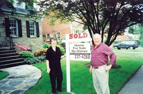 "Happy couple who were able to find a for sale by owner home in front of the house standing next to the ""sold"" real estate sign"